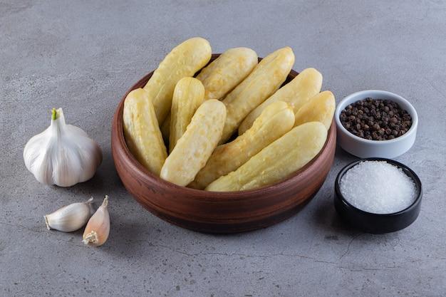 Bol en bois de cornichons de concombre et de grains de poivre sur table en pierre.
