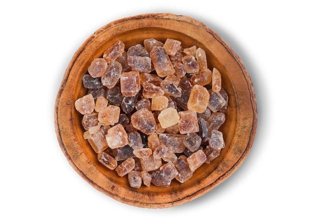 Bol en bois de cubes de sucre caramélisés brun naturel sur blanc.