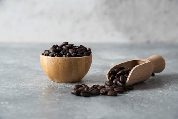 Bol en bois et cuillère de grains de café torréfiés sur marbre.