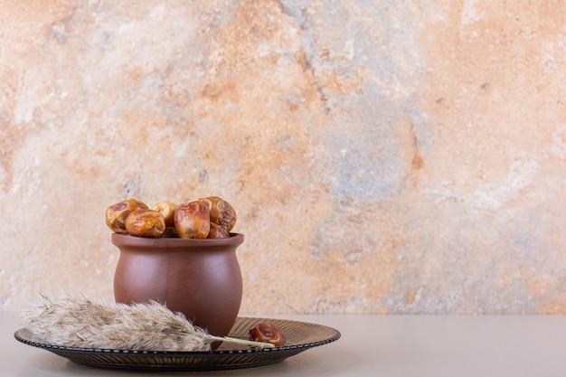 Bol en bois avec des dattes savoureuses séchées sur fond blanc. photo de haute qualité