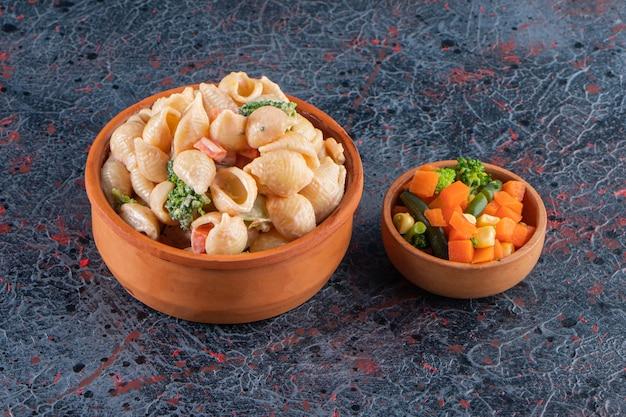 Bol en bois de délicieuses pâtes aux coquillages et mini salade sur une surface en marbre.