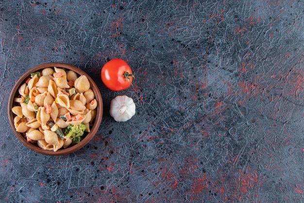 Bol en bois de délicieuses pâtes aux coquillages sur une surface en marbre.