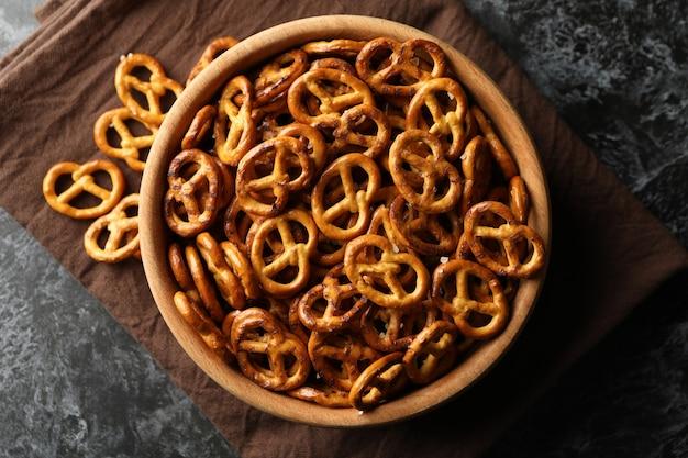 Bol en bois avec de délicieux bretzels craquelins sur serviette