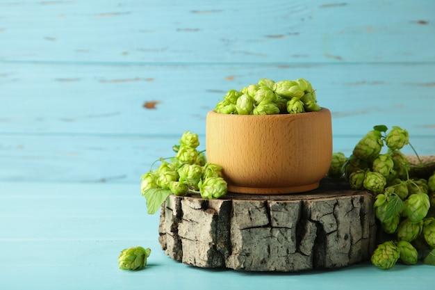 Bol en bois avec du houblon sur fond de bois bleu, espace pour le texte. vue de dessus