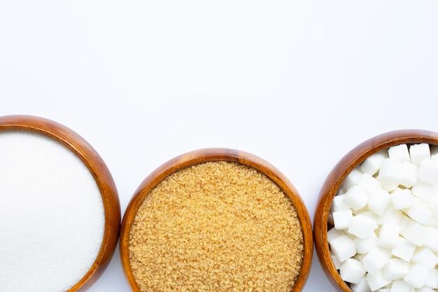 Bol en bois avec du sucre sur fond blanc.