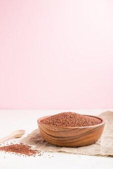 Bol en bois avec des graines de quinoa rouge cru sur fond blanc et rose