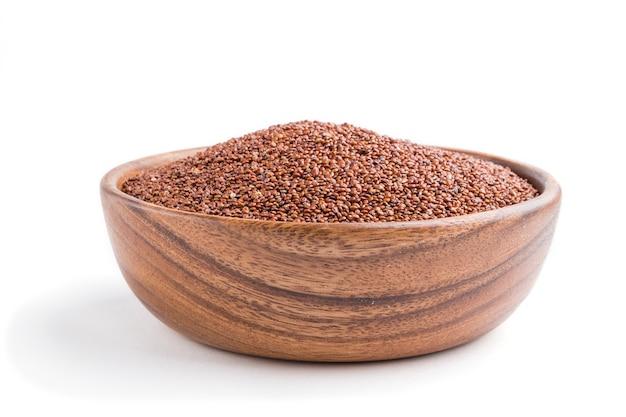 Bol en bois avec des graines de quinoa rouge cru isolé sur une surface blanche