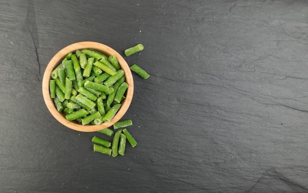 Bol en bois avec haricots verts surgelés vue de dessus