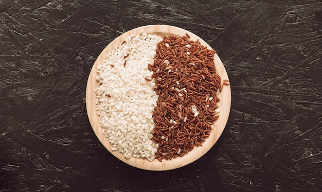 Bol en bois avec jasmin à grain long rouge cru et riz blanc sur fond rugueux