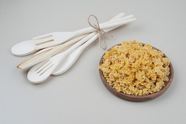 Un bol en bois avec des macaronis crus et des ustensiles de cuisine sur blanc.