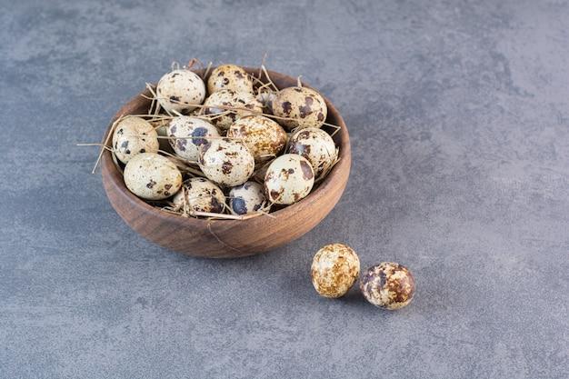 Bol en bois d'oeufs de caille crus sur table en pierre.