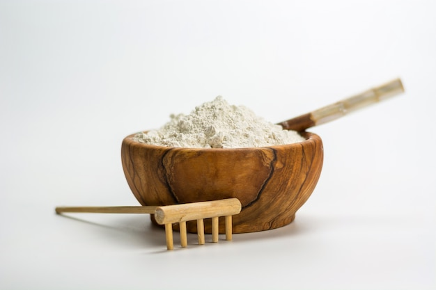 Bol en bois plein d'argile blanche
