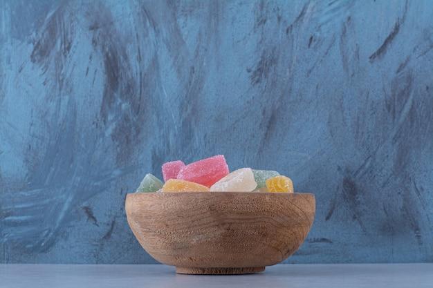 Un bol en bois plein de bonbons aux haricots colorés sur une table grise.