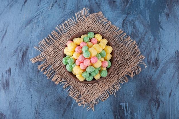 Bol en bois plein de boules de céréales colorées sur bleu.