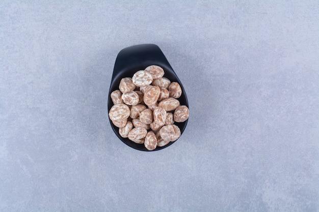 Un bol en bois plein de céréales saines sur une surface grise