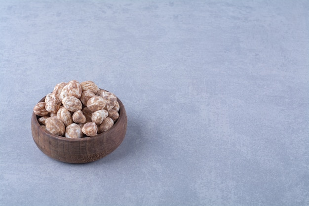 Un bol en bois plein de céréales saines sur une table grise.