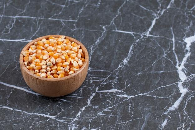 Bol en bois plein de graines de maïs biologiques fraîches sur fond noir.