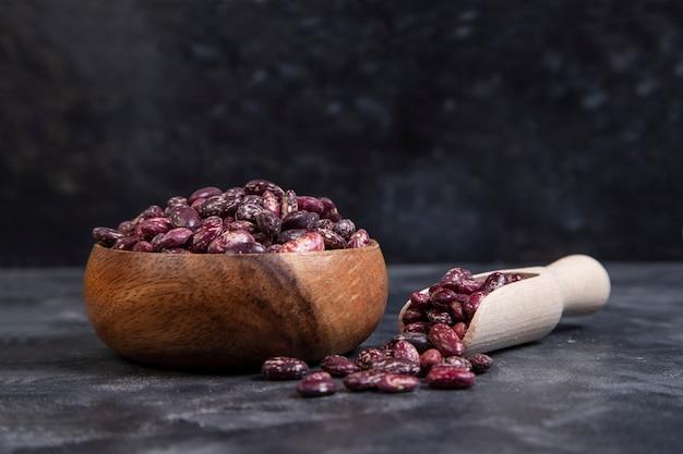 Un bol en bois plein de grains crus de haricots secs sur fond noir
