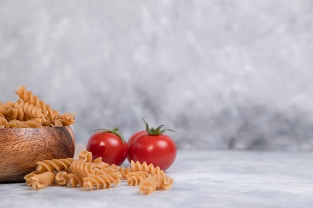 Bol en bois plein de pâtes crues à grains entiers placés sur une table en marbre.