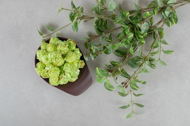 Bol en bois avec une poignée trop remplie d'une portion de pop-corn vert à côté d'une branche de plante décorative sur table en marbre.