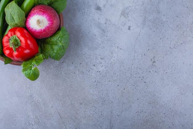 Bol en bois poivron avec radis sur table bleue.