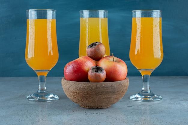 Un bol en bois de pommes avec des tasses en verre de jus d'orange.