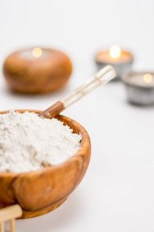 Bol en bois rempli d'argile blanche, idéal pour les soins personnels