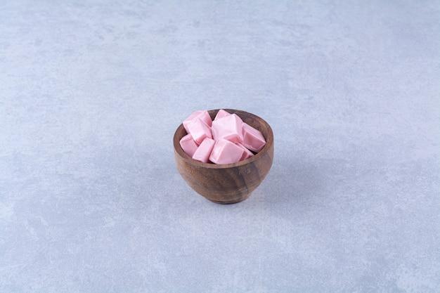 Un bol en bois rempli de confiserie sucrée rose pastila .