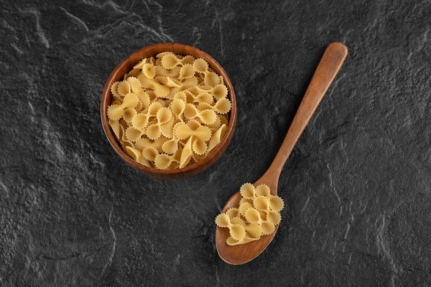Un bol en bois rempli de macaroni farfalle tonde cru.