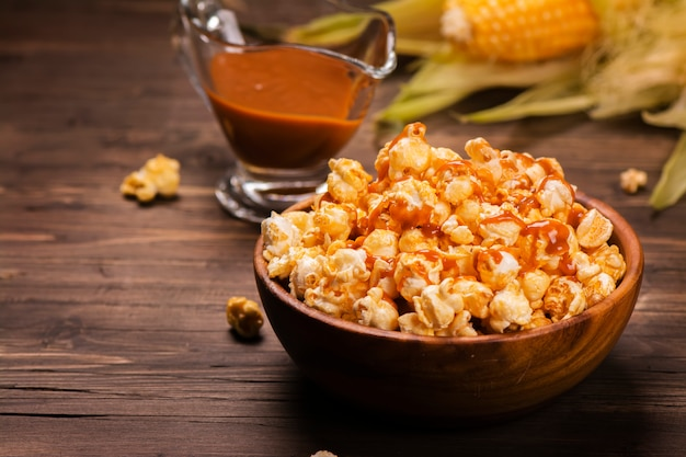 Bol en bois rempli de maïs soufflé au caramel sucré avec sauce au caramel et épis de maïs sur une table rustique. style vintage.