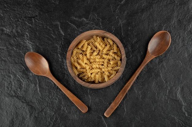 Un bol en bois rempli de pâtes crues à la girandole.