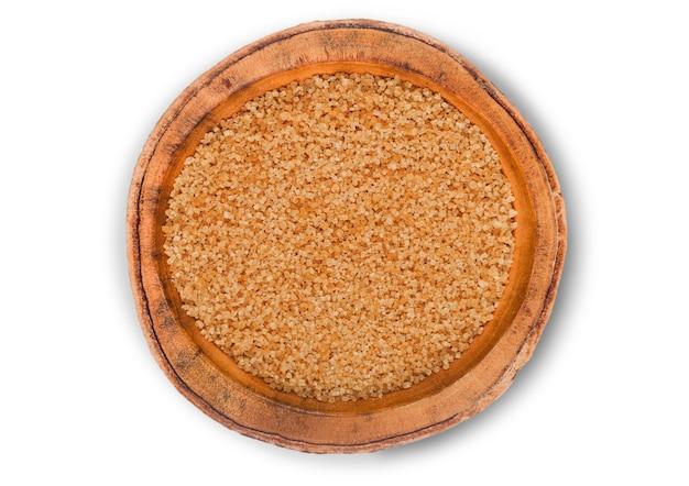 Bol en bois de sucre raffiné brun naturel sur blanc.
