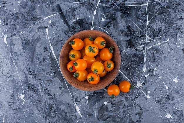 Bol en bois de tomates cerises fraîches sur fond de marbre.