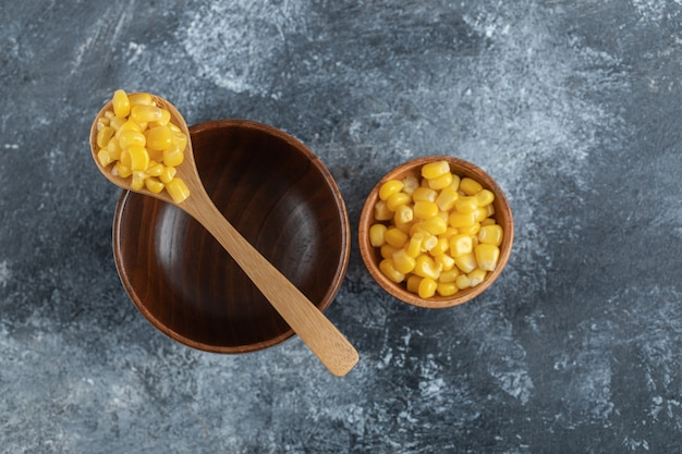 Un bol en bois vide avec une cuillère en bois de graines de maïs soufflé.