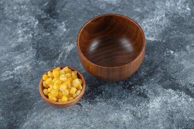 Un bol en bois vide avec un petit bol de graines de maïs soufflé.