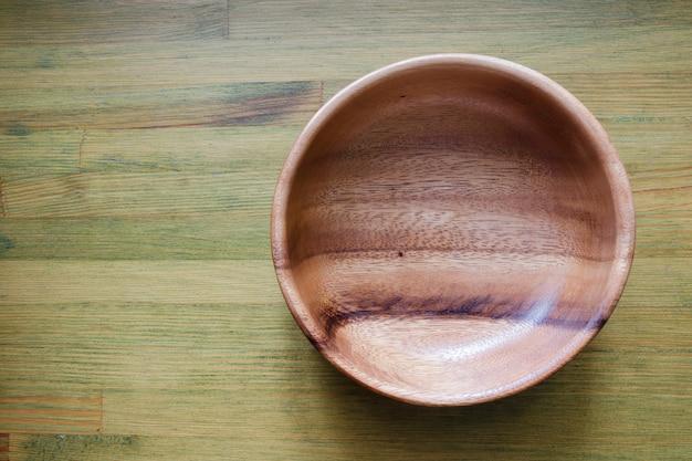 Bol en bois vide sur table en bois verte