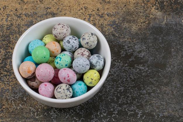 Bol de bonbons colorés sur marbre.