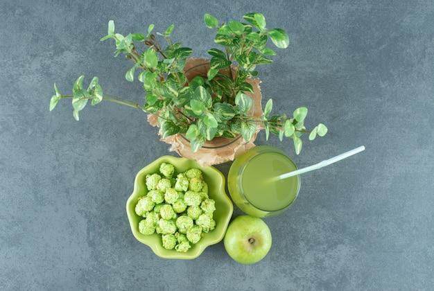 Bol de bonbons pop-corn, verre de jus de pomme, pomme unique et un wase enveloppé avec une plante décorative sur fond de marbre. photo de haute qualité