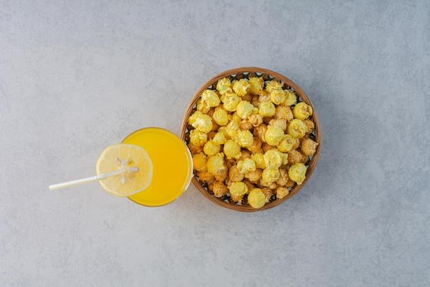 Bol de bonbons pop-corn et un verre de jus avec une tranche de citron sur une surface en marbre