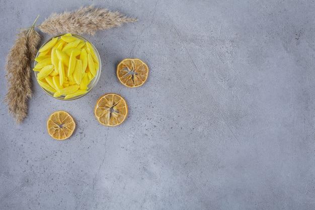Bol de bonbons sucrés jaunes et de citrons tranchés sur pierre.