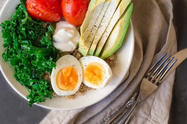 Bol de bouddha de quinoa avec des tomates cuites au four, des œufs durs de chou frisé d'avocat et du yogourt grec