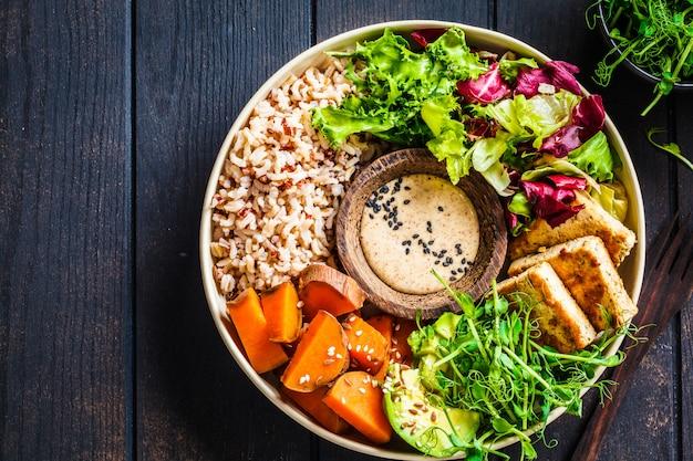 Bol de bouddha avec tofu, avocat, riz, plants, vinaigrette à la patate douce et au tahini.