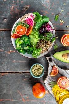 Bol bouddha vegan avec fruits, légumes et graines. nourriture équilibrée. délicieux régime de désintoxication. vue de dessus. image verticale