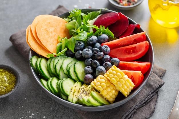 Bol de bouddha végétalien avec légumes et fruits servis dans un bol sur fond gris. fermer