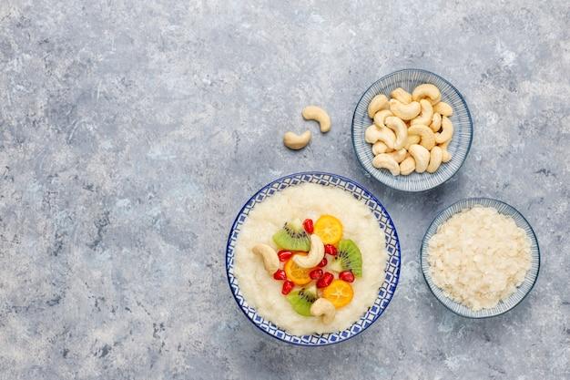 Bol de bouillie de flocons de riz avec des tranches de kiwi, des graines de grenade, des cumquats et des noix de cajou, vue de dessus