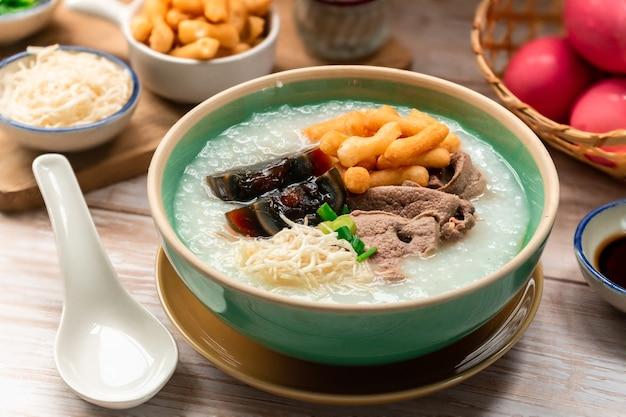 Bol de bouillie de riz avec œuf centenaire et bâton de pâte frite croustillante appelé apéritif du matin patongo thai
