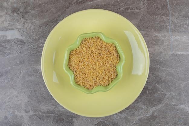 Un bol de boulgour sur l'assiette, sur la surface en marbre