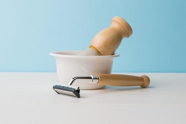 Un bol avec une brosse et un rasoir avec un manche en bois sur une table blanche sur fond bleu.