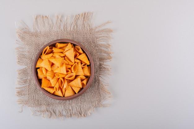 Bol brun de chips triangle sur fond blanc. photo de haute qualité