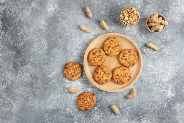 Bol de cacahuètes et biscuits aux cacahuètes biologiques sur table en marbre.